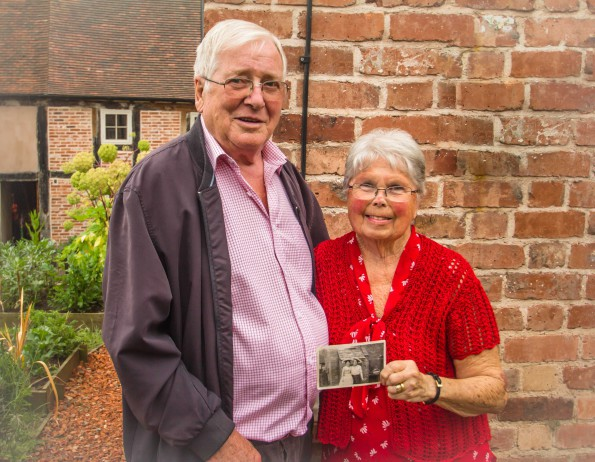 An older man and woman stand together holding a black and white photo