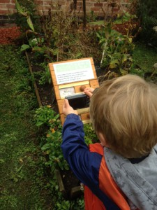 A young child looking at a wooden sign with sliding panels