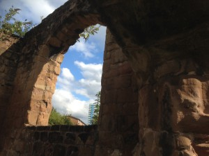a block of flats in the distance through the ruined window arch