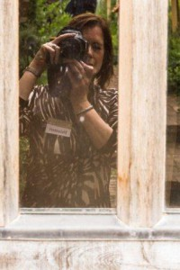 A woman taking a photo of her reflection in the Weaver's House window