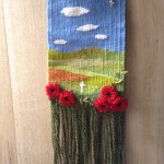 a wall hanging depicting blue sky, fields and red poppies