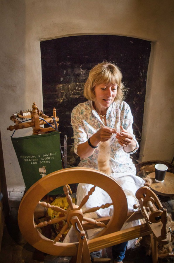 A woman using a traditional spinning wheel