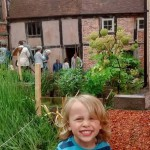 a young boy smiling in the garden of the weaver's house