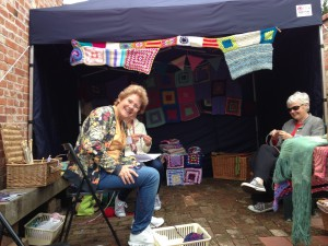 a group of women knitting with colourful array of knitted and crocheted work