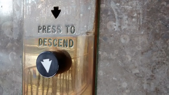 press to descend brass lift button