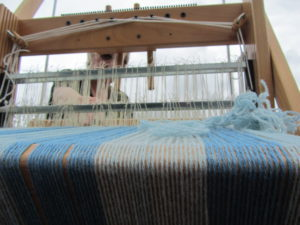 small table loom with blue cloth being woven
