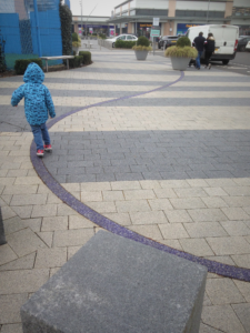 a child walking on a strip of blue gravel