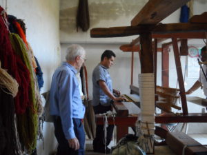 A man uses a large floor stadning loom, observed by another man