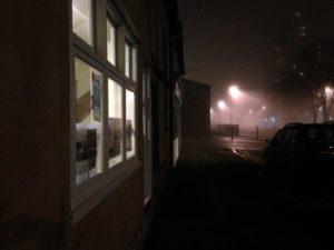 a small window cast light onto a misty street