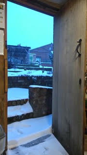 The door from the Weaver's House into a snow covered garden