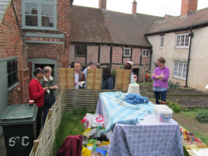 Table covered with woven textiles and wool, lots of people in the garden