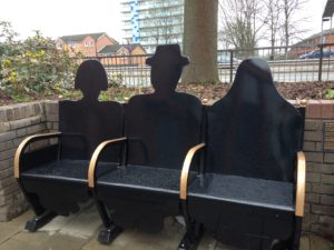 A three seater bench representing three seated figures in silhouette; one with short bobbed hair, one with a brimmed hat and one with a hijab.