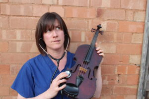 Dr Jenny holds a stethoscope to a violin