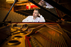 a man sitting at a grand piano