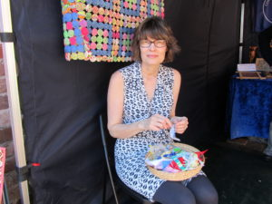 Lady holding a basket of colourful yarn