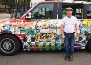 A man stands next to a taxi decorated with scenes of Coventry