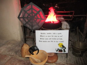 A paper cobweb hangs by a fiery cauldron in the Weaver's House