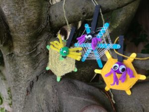 Colourful pom pom spiders on woven webs