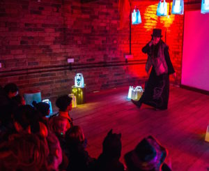 Woman in long coat and top hat, lit with orange light performs to children