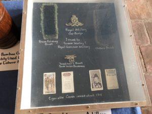 Brass polishing brush, badges and cigarette cards