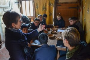 A group of teenagers sit around a replica medieval table listening to volunteer