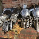 On a table, shiny armoured gauntlets gleam in the sun