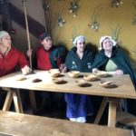Medieval costumed reenactors sit around the replica table in the Weaver's House