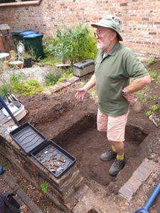 A man stands in a small excavated area