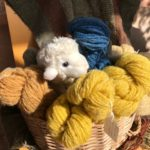Cuddly toy sheep peeps out among skeins of wool