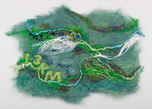 Textile art in blues and greens reminiscent of water, includes text '13KM'