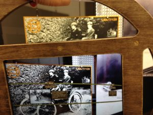 an ipad with a wooden wheel frame is held over an old photo, revealing interactive details