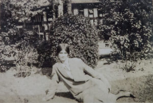 A old sepia photo showing a woman in front of a half timbered building