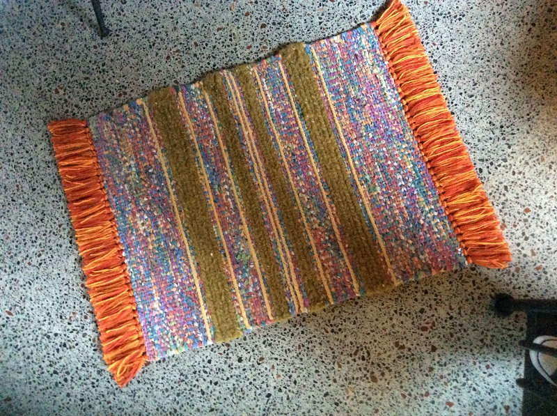 striped rug, colourful mixed wool and ornage fringe