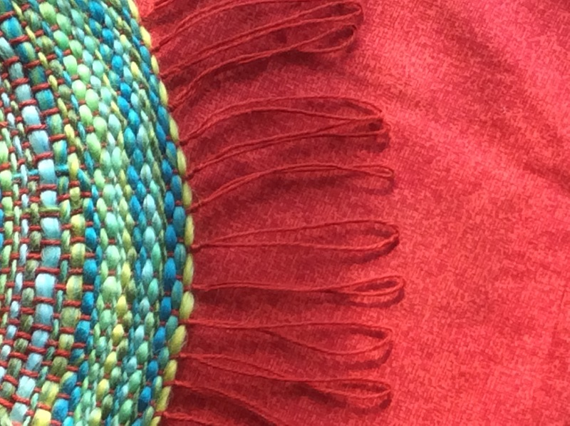detail of cushion cover, red background, edge of circular motif in blues
