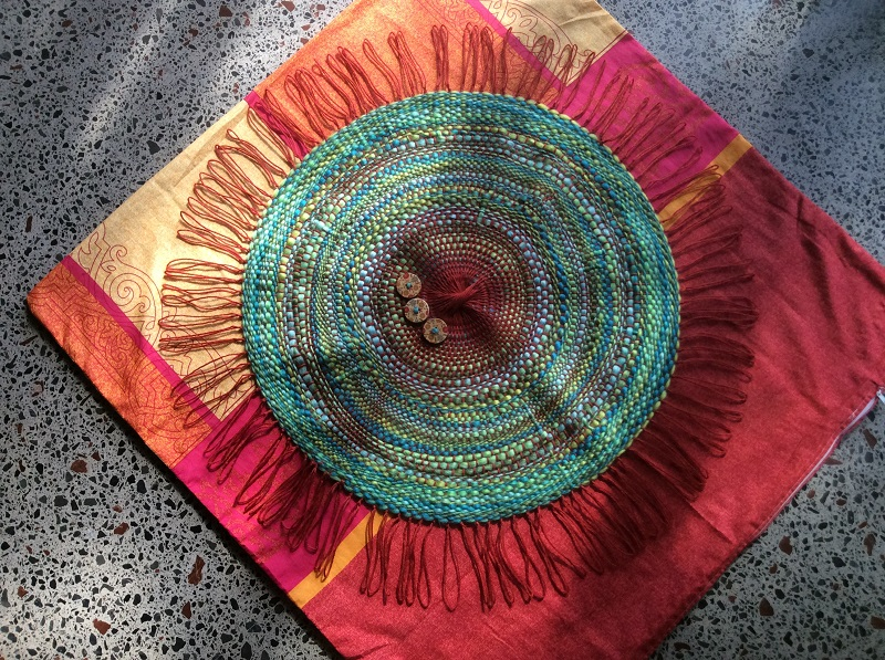 cushion cover, red and gold with a central circular motif in shades of blue