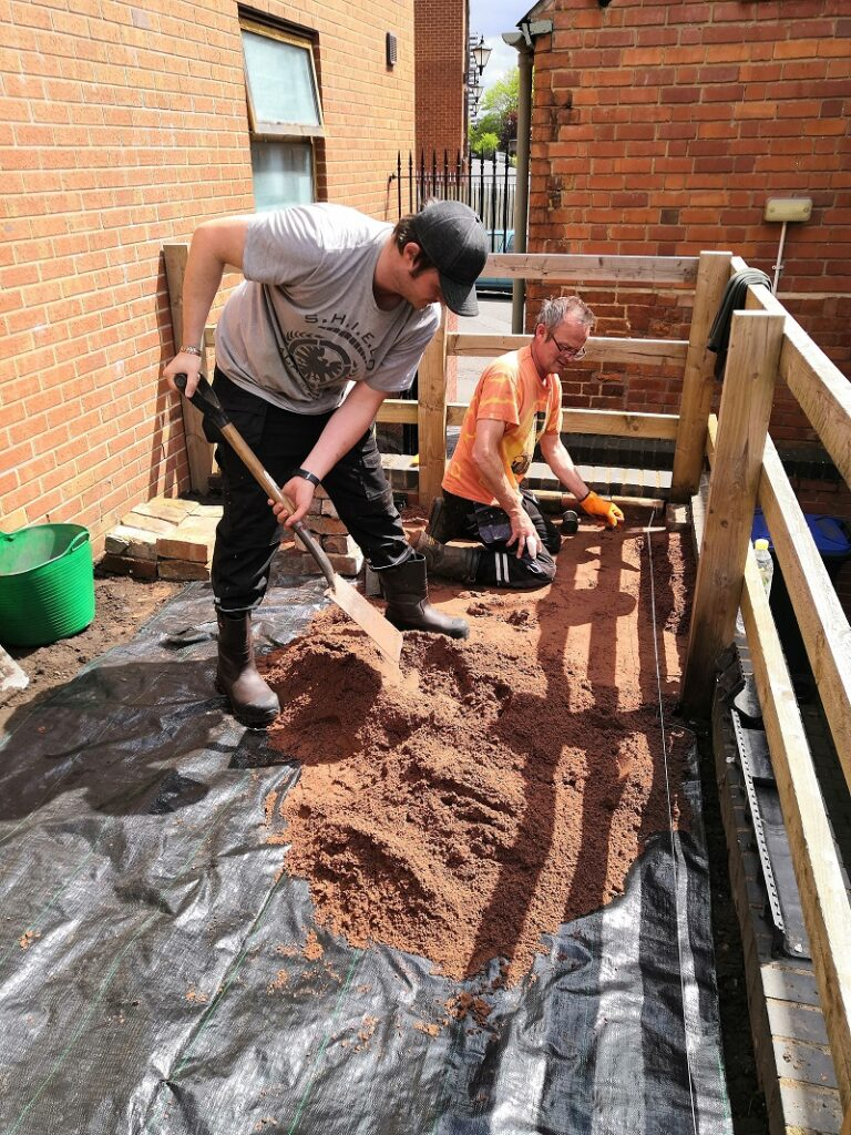 Two men spreading building sand