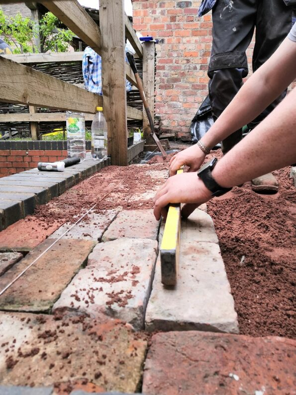 hands levelling off bricks