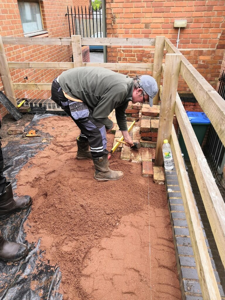 a man laying bricks over sand layer