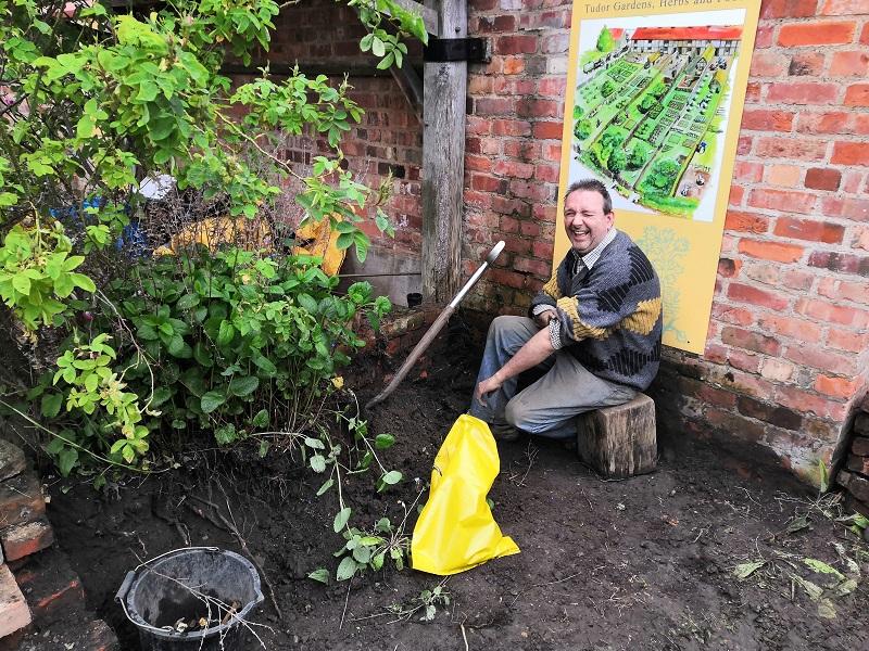 a smiling man digging the garden